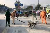 CSGT quét bùn, cát trên đường cho dân khỏi té ngã