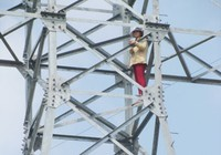 Một phụ nữ trèo trụ điện đòi đền bù đất