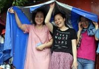 Phụ huynh đội mưa chờ con ngoài phòng thi