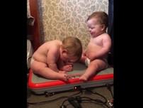 2 em bé ngồi trên máy rung lắc vui nhộn