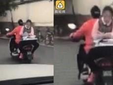 Clip: Nữ sinh ngồi ngược sau xe máy làm bài tập