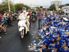 Clip: Hàng trăm thùng bia trên xe tải đổ xuống dốc cầu vượt Gò Dưa