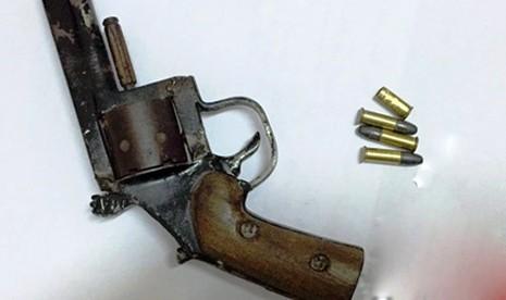 Khẩu súng và đạn bị thu giữ.