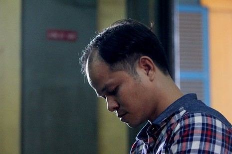 Bị cáo Minh cúi đầu chăm chú lắng nghe phần tranh luận của luật sư Hùng