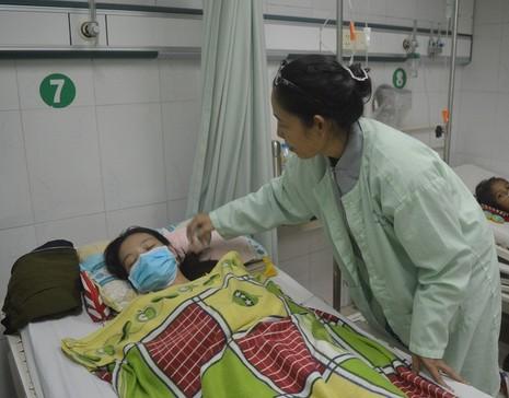 Chị Huỳnh Thị Minh Lam, mẹ của Gia Linh đang chăm sóc cho em khi còn nằm điều trị tại BV. ẢNH: THANH TUYỀN.