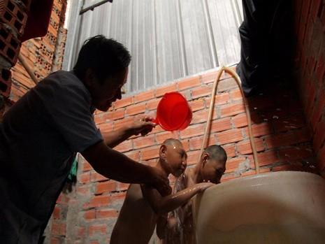 Trở lại công việc thường ngày, hai giờ chiều anh Nghị tắm cho các con để chuẩn bị cho chúng ăn cơm trước khi đi bán kẹo.