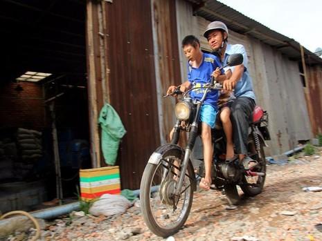 Ba cha con đèo nhau trên chiếc xe máy cà tàng