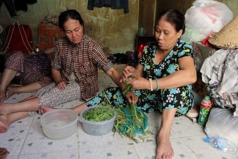 Chị Đào Thị Lê - vợ anh Tiến (bìa phải) đang chuẩn bị bữa cơm cho cả gia đình.