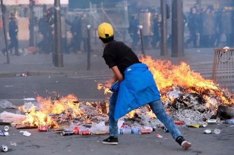 Một fan bóng đá ném đá về phía cảnh sát tại Paris ngày 10-7.
