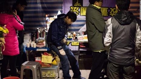 Lãnh đạo biểu tình Joshua Wong (ngồi) trong ngày tuyệt thực thứ 5 trong đợt biểu tình Hong Kong năm 2014.