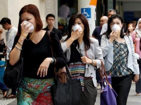 Người dân Singapore mang khẩu trang chống bụi sáng 26-8 vì ảnh hưởng cháy rừng ở Indonesia.