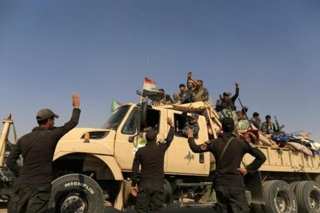 Lính đặc nhiệm Iraq vẫy tay với cảnh sát Iraq đang trên đường tiến về Mosul ngày 26-10.