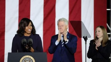 Đệ nhất phu nhân Michelle Obama cùng cựu Tổng thống Bill Clinton và cô Chelsea đứng trong làn kính chắn đạn trên sân khấu vận động cho bà Clinton tại Philadelphia ngày 7-11.