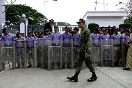 Hàng rào cảnh sát canh giữ ngoài cổng nghĩa trang anh hùng dân tộc Philippines trong lúc diễn ra lễ mai táng di hài ông Marcos ngày 18-11.