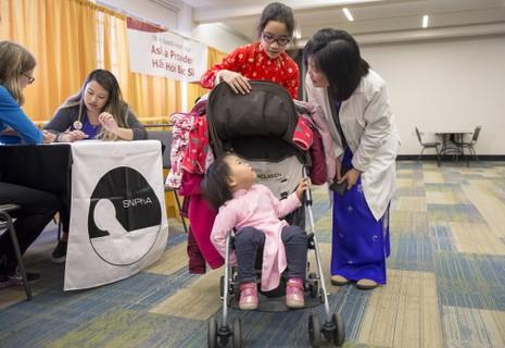 Chị Karen Smith (trái)nhận kết quả kiểm tra sức khỏe tại triển lãm y tế, một phần của chuỗi hoạt động Tet in Seattle ngày 22-1, trong khi các con chị trò chuyện với y tá. Ảnh: SEATTLE TIMES