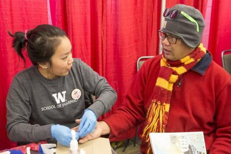 Cecilia Phạm, sinh viên năm nhất tại ĐH Dược Washington, kiểm tra lượng cholesterol và đường trong máu cho ông Jim Kaanana ngày 22-1. Ảnh: SEATTLE TIMES