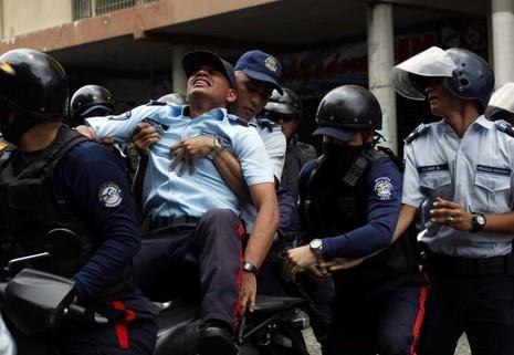 Cảnh sát đưa một đồng nghiệp bị thương trong xung đột với người biểu tình đi cấp cứu, tại San Cristobal, tỉnh bang Bolivar (Venezuela) ngày 19-4. Ảnh: REUTERS