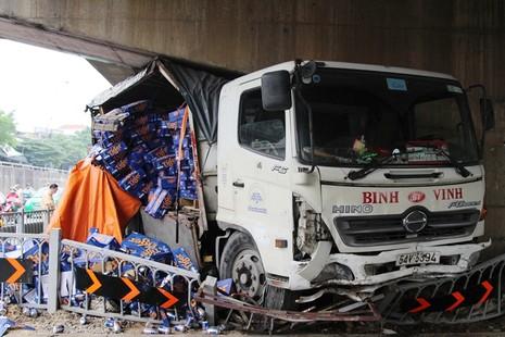 Chiếc xe tải chở bia mất thắng lao vào gầm cầu vượt Linh Xuân khiến hàng chục thùng bia đổ xuống đường