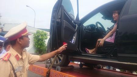 Xe cẩu chở ô tô cùng nữ tài xế cố thủ bên trong về đồn - ảnh 1