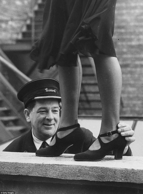 Một nhân viên làm việc ở ga tàu hỏa được giao nhiệm vụ làm giám khảo tại một cuộc thi tìm kiếm Hoa hậu mắt cá chân được tổ chức dành riêng cho những phụ nữ làm việc trong ngành đường sắt Anh hồi năm 1949.