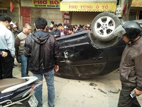 Va chạm với xe máy, ô tô lật ngửa giữa đường - ảnh 1