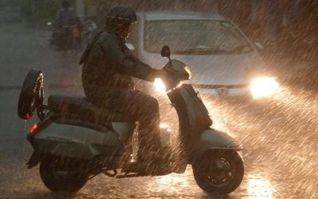 Người dân Ấn Độ đi lại trong mưa bão ở thành phố Amritsar.