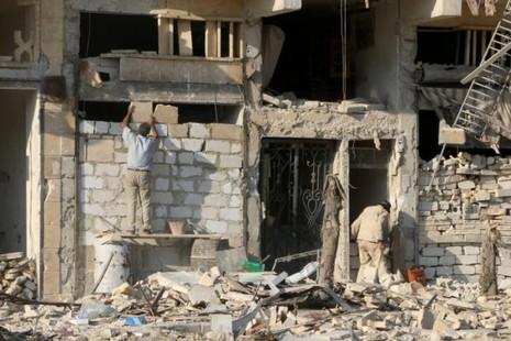 Một người đàn ông đang xây lại tường nhà của một tòa nhà bị hư hỏng ở khu vực al-Katerji ở Aleppo, Syria ngày 13-8-2016. Ảnh: Reuters