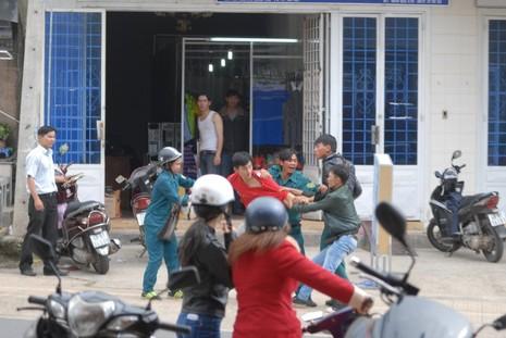 Nữ dân quân tự vệ và một người trong nhóm dân quân tự vệ cố can ngăn vụ ẩu đả nhưng không thành