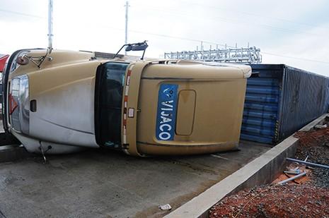 Xe container 'vấp' dải phân cách lật nghiêng, 13 tấn bánh ngập nước - ảnh 1