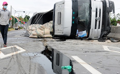 Xe tải lật nghiêng, xi măng, dầu nhớt tràn ra quốc lộ - ảnh 1