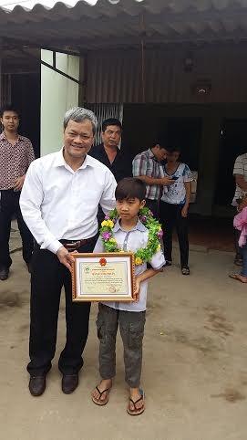 Ông Nguyễn Tử Quỳnh phó chủ tịch thường trực UBND Tỉnh trao bằng chứng nhận cho em Vĩnh