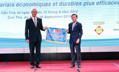 Chủ tịch UBND TP Cần Thơ Võ Thành Thống (bìa phải) trao cờ đăng cai Hội nghị lần thứ 11 cho đại diện TP Toulouse