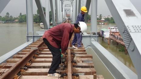 Công nhân hoàn thiện lắp ray chạy tàu trên mặt cầu Ghềnh vừa được lắp xong ba nhịp.