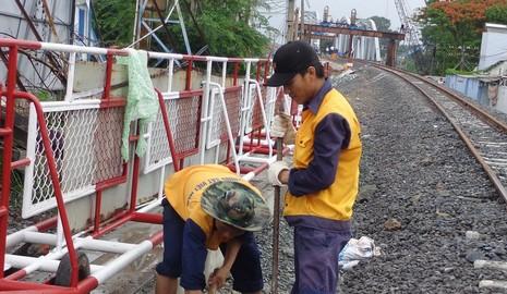 Công nhân hoàn thiện hệ thống thoát nước, gác chắn trên đường Bùi Hữu Nghĩa, thành phố Biên Hòa ở bờ Nam cầu Ghềnh mới để phục vụ cho tàu chạy thử từ ga Dĩ An ra trong chiều nay.