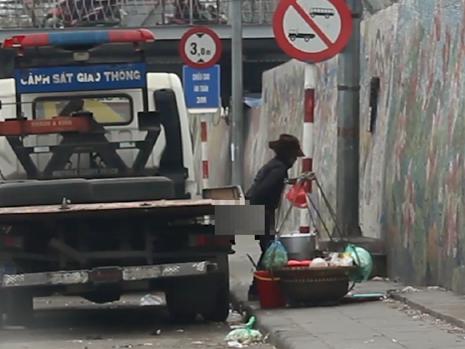 Một phụ nữ bán hàng rong vô tư tè bậy tại khu vực gầm cầu Long Biên.