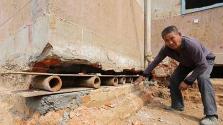 Một công nhân đặt tấm ván lên những ống sắt ngắn trong khe tường của một bệnh viên ở thành phố Trịnh Châu, tỉnh Hà Nam, Trung Quốc hôm 8/4.