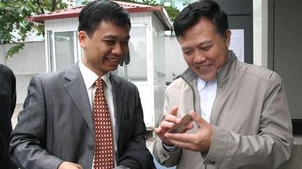 Ông Nguyễn Văn Quyền (phải) chúc mừng anh Cường, người đầu tiên nhận GPLX qua khai báo điện tử.