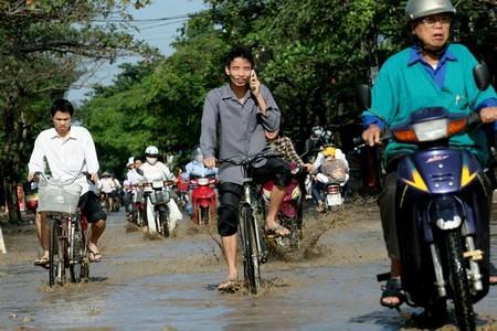 Mải mê nói chuyện điện thoại trong khi vượt đoạn đường ngập nước.