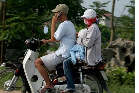 Không mũ bảo hiểm, chở theo trẻ em vẫn thản nhiên sử dụng điện thoại trên Đại Lộ Thăng Long.