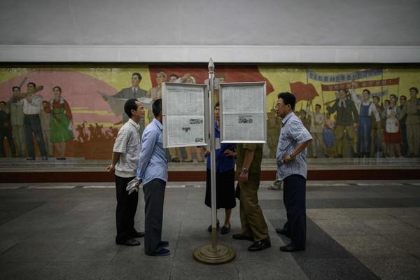 Người dân Bình Nhưỡng (Triều Tiên) đọc báo về cuộc thượng đỉnh lịch sử Mỹ-Triều, ngày 12-6. Ảnh: GETTY IMAGES