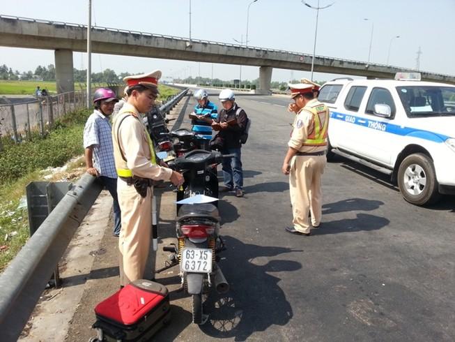 Liều lĩnh khiêng xe máy qua hàng rào vào chạy… đường cao tốc