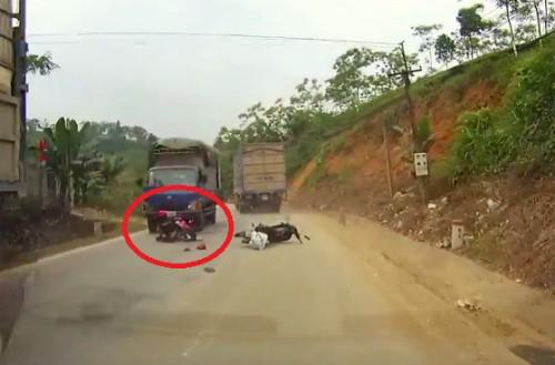 Thoát chết khó tin khi xe máy vượt ẩu giữa 2 xe tải