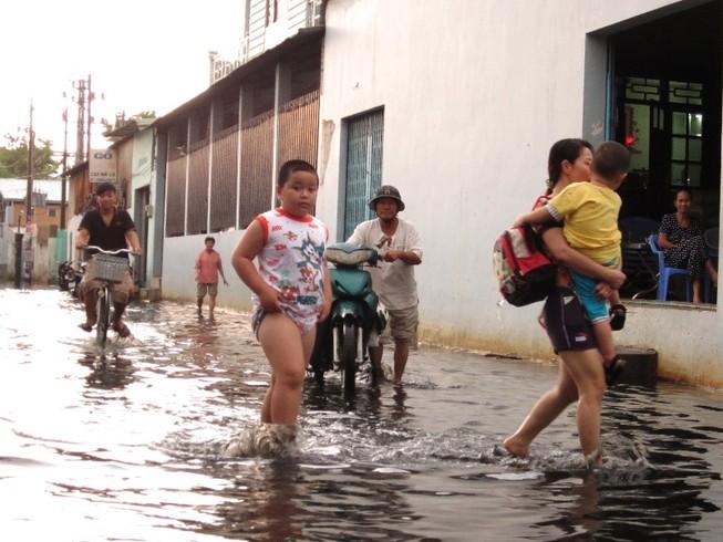 TP.HCM: Sau mưa, người dân bì bõm lội nước cống đen ngòm