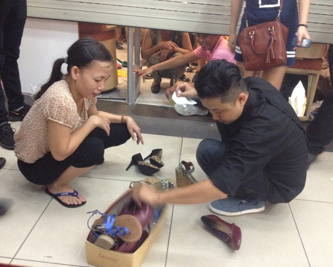 Xả hàng đồng giá, người dân 'chui' cửa cuốn để mua giày