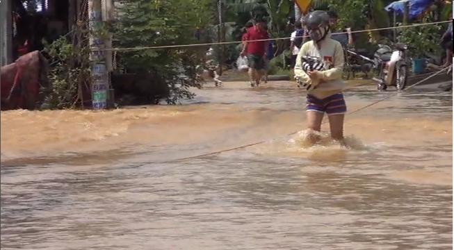 Biên Hòa ngập lụt, người dân giăng dây để đi về nhà