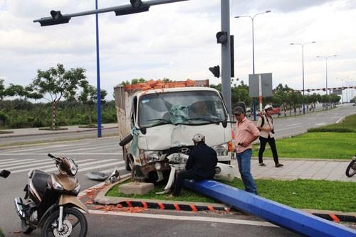 Húc xe taxi, xe tải chở gạch tông gãy trụ đèn