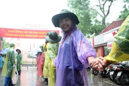 Tình nguyện viên đội mưa che chắn cho sĩ tử