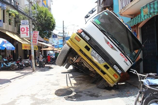 Xe tải sụp hố ga lật chổng vó giữa phố Sài Gòn