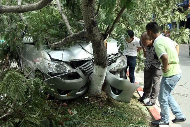 Innova 7 chỗ bẹp dúm sau khi tông gẫy đôi cây trên phố Hà Nội