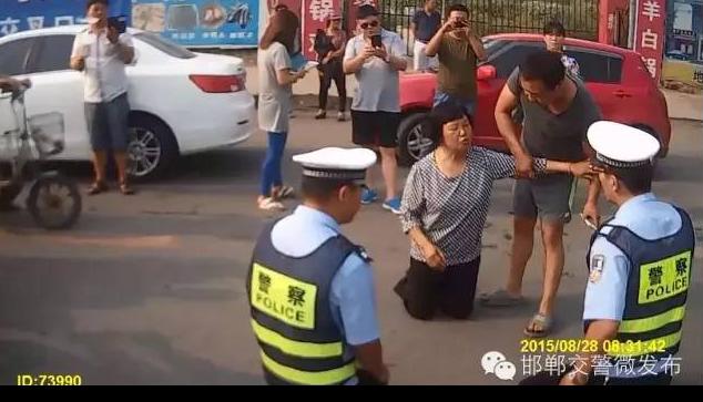 Cảnh sát giao thông quỳ xuống đất để giải thích cho dân